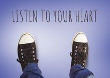 Escute seus texto do coração e sapatas pretas nos pés com fundo roxo Fotos de Stock