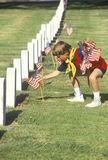Escuteiro de Cub que põr bandeiras americanas sobre os veteranos graves Fotografia de Stock Royalty Free