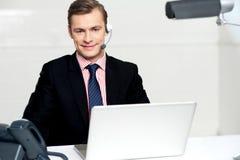 Esecutivo del centro di chiamata che propone con le cuffie avricolari Immagini Stock