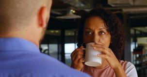 Esecutivo femminile mangiando caffè in self-service 4k archivi video