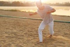 Esecutore atletico di capoeira che fa i movimenti sulla spiaggia Fotografia Stock Libera da Diritti