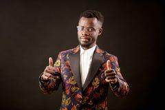 Esecutore ben vestito africano che sfoglia su isolato sui precedenti neri immagine stock