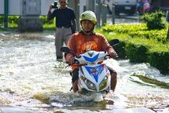 Esecuzione della motocicletta tramite la strada sommersa Fotografie Stock Libere da Diritti
