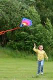 Esecuzioni della ragazza del bambino con il cervo volante Fotografie Stock