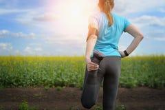 Eseguendo allungamento - smartwatch d'uso del corridore della donna Fotografia Stock Libera da Diritti