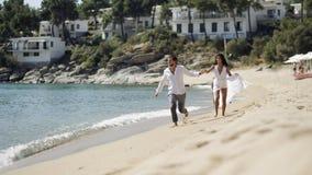Eseguendo le coppie sposate appena sulla spiaggia nell'ora legale, il giorno soleggiato, ha umore felice Fondo di vista sul mare immagine stock libera da diritti