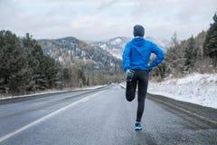 Eseguire allungamento Atleta alla cima della montagna Immagine Stock
