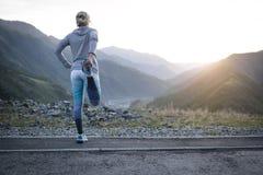 Eseguire allungamento Atleta alla cima della montagna Fotografie Stock