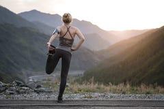 Eseguire allungamento Atleta alla cima della montagna Fotografia Stock