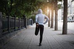 Eseguire allungamento Atleta della donna su una via della città che fa i exercis Fotografia Stock