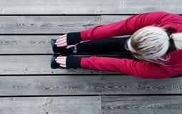 Eseguire allungamento prima dell'correre sul pavimento di legno Immagine Stock Libera da Diritti