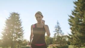 Eseguire donna che pulisce sudore dalla fronte alla mattina che pareggia nel parco video d archivio