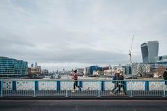 Eseguire donna ed i pedoni sul ponte di Londra, Londra, Regno Unito fotografia stock libera da diritti