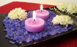 Esencial del balneario (sal, velas y flores violetas) Imagenes de archivo