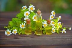 Esencja kwiaty na stole w pięknej szklanej butelce zdjęcie royalty free