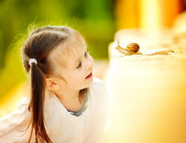 Eseniya and snail. Photo made in summer in daylight Stock Photos