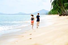 esercitarsi Coppie felici che funzionano sulla spiaggia Sport, forma fisica guar Fotografia Stock