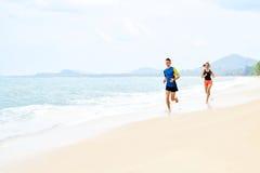 esercitarsi Coppie felici che funzionano sulla spiaggia Sport, forma fisica guar Immagini Stock