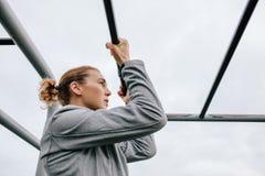 Esercitazione atletica della donna all'aperto sulle attrezzature di forma fisica Fotografia Stock