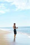 Esercitazione dell'uomo all'aperto, facendo esercizio di allenamento alla spiaggia Forma fisica Fotografia Stock