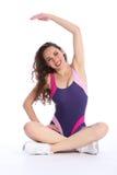 Esercitazione felice adatta di stirata della donna durante l'allenamento Fotografia Stock