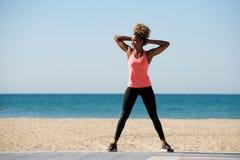 Esercitazione femminile afroamericana integrale alla spiaggia Fotografia Stock