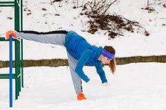 Esercitazione urbana d'uso degli abiti sportivi della donna fuori durante l'inverno Fotografia Stock