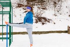 Esercitazione urbana d'uso degli abiti sportivi della donna fuori durante l'inverno Immagini Stock