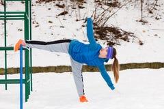 Esercitazione urbana d'uso degli abiti sportivi della donna fuori durante l'inverno Immagine Stock