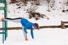 Esercitazione urbana d'uso degli abiti sportivi della donna fuori durante l'inverno Immagine Stock Libera da Diritti