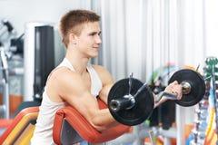 Esercitazioni del muscolo del bicipite di allenamento dell'uomo del Bodybuilder Immagine Stock