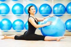 Esercizi d'allungamento spaccati con la palla di forma fisica Fotografia Stock Libera da Diritti