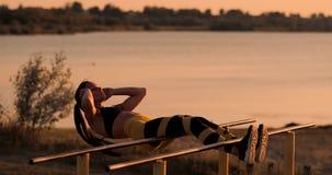 Esercizi dei muscoli addominali Una giovane bellezza atletica al tramonto contro il lago nella donna di estate nel fare degli abi archivi video