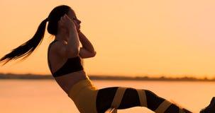 Esercizi dei muscoli addominali Una giovane bellezza atletica al tramonto contro il lago nella donna di estate nel fare degli abi stock footage