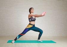 Esercizi dell'interno di yoga e di forma fisica di allenamento della donna che allungano corpo Immagini Stock