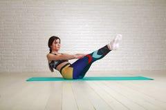 Esercizi dell'interno di yoga e di forma fisica di allenamento della donna che allungano corpo Fotografie Stock