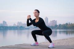 Esercizi della giovane donna sul pilastro durante l'addestramento di mattina Fotografie Stock