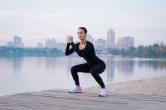 Esercizi della giovane donna sul pilastro durante la forma fisica di mattina Fotografie Stock