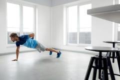 Esercizi di allenamento dell'uomo Forma fisica Doing Push Ups di modello maschio all'interno Immagini Stock