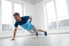Esercizi di allenamento dell'uomo Forma fisica Doing Push Ups di modello maschio all'interno Fotografia Stock