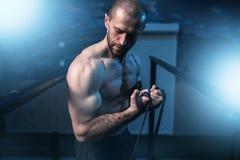 Esercizi di athlet del muscolo con la banda elastica Fotografie Stock Libere da Diritti