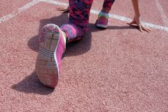 Esercizi di sport ed allungare o preparare un corridore iniziare allo stadio Una giovane bella ragazza dalla carnagione scura in  fotografia stock libera da diritti