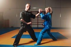 Esercizi maschii e femminili dei combattenti di wushu dell'interno Immagine Stock