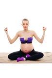 Esercizi prenatali Donna incinta bella che si esercita mentre sedendosi nella posizione di loto Fare della donna incinta relativo Fotografia Stock