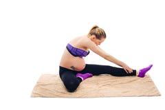 Esercizi prenatali Donna incinta bella che si esercita mentre sedendosi nella posizione di loto Fare della donna incinta relativo Immagini Stock