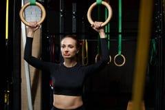 Esercizi sugli anelli allenamento in palestra scura Fotografia Stock