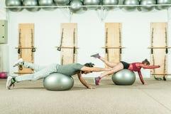 Esercizio acrobatico estremo di giovane bello di forma fisica allenamento delle coppie sulla palla come preparazione per la conco Fotografia Stock