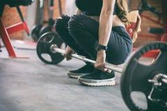 Esercizio asiatico della donna di giovane forma fisica con l'incrocio a macchina del cavo immagini stock libere da diritti