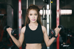 Esercizio asiatico della donna di giovane forma fisica con l'incrocio a macchina del cavo immagine stock