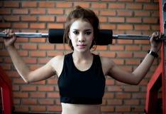 Esercizio asiatico della donna di giovane forma fisica con l'incrocio a macchina del cavo fotografie stock libere da diritti